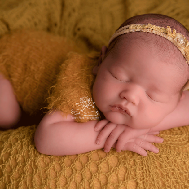 newborn baby in yellow. gifts to buy new mums